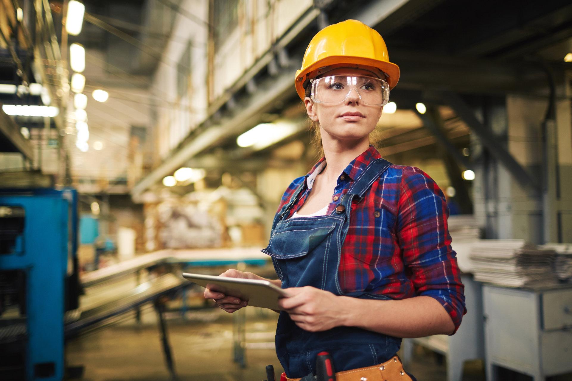 femeie in echipament de lucru (salopeta, casca, ochelari de protectie) intr-o uzina/fabrica; chemare la implicarea voluntarilor, mentorilor, consilierilor vocationali