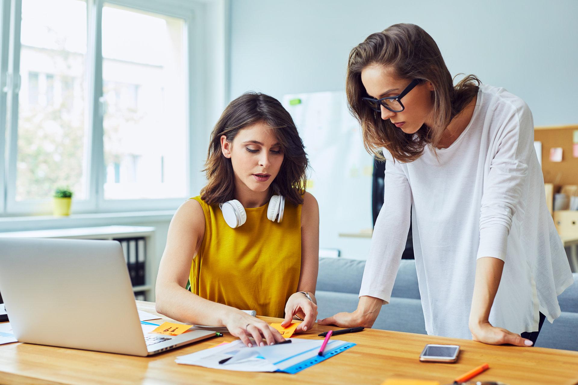 consiliere vocationala sau in cariera; doua femei asezate langa o masa cu un laptop, discuta despre rezultatele testului vocational